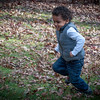 Young african-american boy running in the yard with leaves all around.