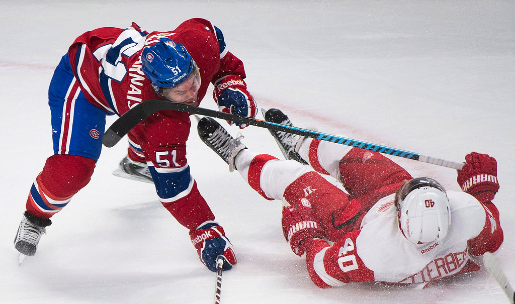 . Montreal Canadiens\' David Desharnais (51) collides with Detroit Red Wings\' Henrik Zetterberg during first period NHL hockey action in Montreal, Tuesday, Oct. 21, 2104. (AP Photo/The Canadian Press, Graham Hughes)