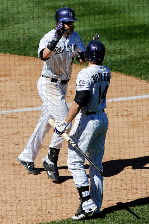 . Colorado Rockies\' Charlie Blackmon, left, is congratulated by Josh Rutledge (14) after hitting a solo home run against the Los Angeles Dodgers during the third inning of a baseball game Wednesday, Sept. 17, 2014, in Denver. (AP Photo/Jack Dempsey)