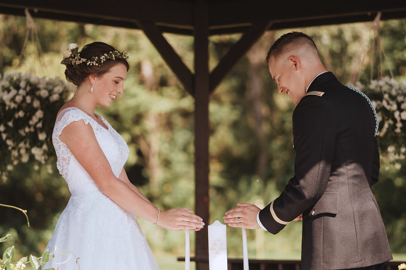 Bride and groom smile as they light unity candles together.