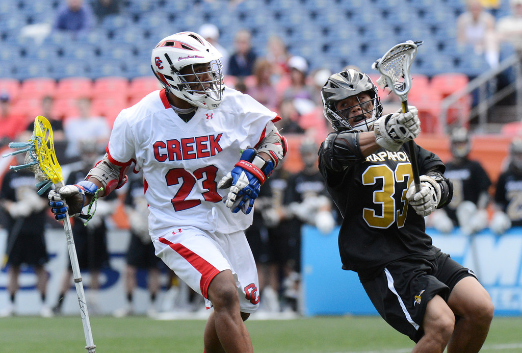 . DENVER, CO. - MAY 18 : Brandon Willis of Cherry Creek High School (23) controls the ball against Peter Neenan of Arapahoe High School (33) during 5A Boy\'s Lacrosse Championship game at Sports Authority Field at Mile High Stadium. Denver, Colorado. May 18, 2013. Arapahoe won 10-7. (Photo By Hyoung Chang/The Denver Post)