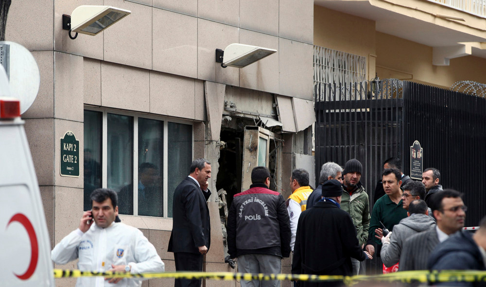 . Emergency personnel are seen in front of a side entrance of the U.S. Embassy in the Turkish capital, Ankara, after a suspected suicide bomber detonated an explosive device, Friday Feb. 1, 2013. The bomb appeared to have exploded inside the security checkpoint at the entrance of the visa section of the embassy. A police official said at least two people are dead. (AP Photo/Burhan Ozbilici)