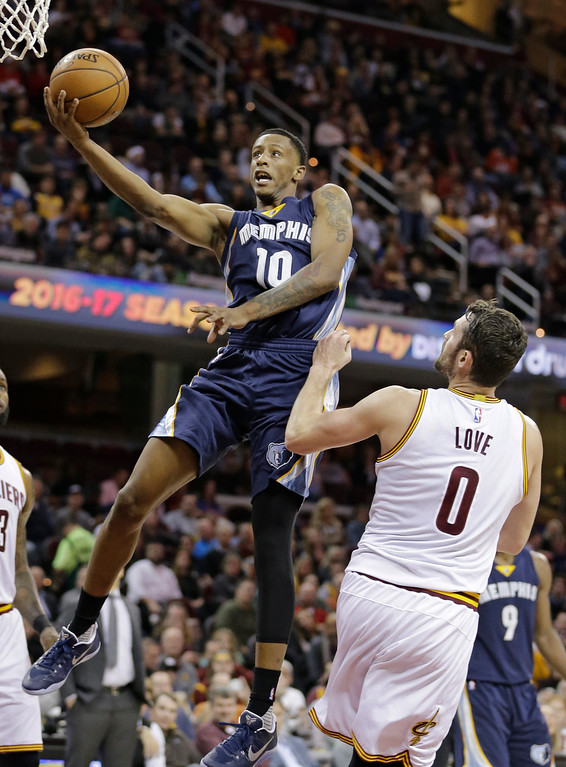 . Memphis Grizzlies\' Troy Williams (10) shoots over Cleveland Cavaliers\' Kevin Love (0) in the second half of an NBA basketball game, Tuesday, Dec. 13, 2016, in Cleveland. The Cavaliers won 103-86. (AP Photo/Tony Dejak)