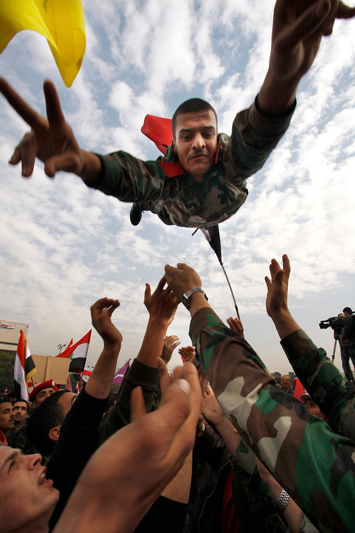 . FILE - A Syrian solider flashes the victory sign as he is thrown in the air during a rally at Umayyad Square in Damascus, Syria, Wednesday, Dec. 21, 2011. (AP Photo/ Muzaffar Salman, File)