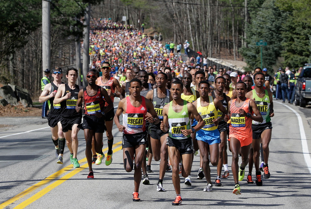 . Yemane Tsegay, left center, and Deribe Robi, right center, both of Ethiopia, lead the pack of runners just after the start in Hopkinton, Mass., of the 120th Boston Marathon on Monday, April 18, 2016. (AP Photo/Steven Senne)