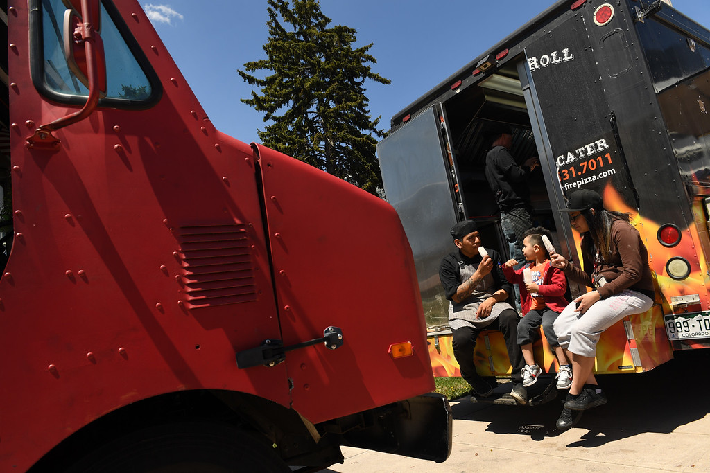 . JT Tapia, far left, enjoys a popsicle with his son Jobe, 5, middle and wife Dawn Marie, right, as he takes a break from working at Wheels On Fire, a wood-fired food truck, at Civic Center Park on the first day of the 11th annual Civic Center EATS on May 3, 2016 in Denver, Colorado.  (Photo by Helen H. Richardson/The Denver Post)