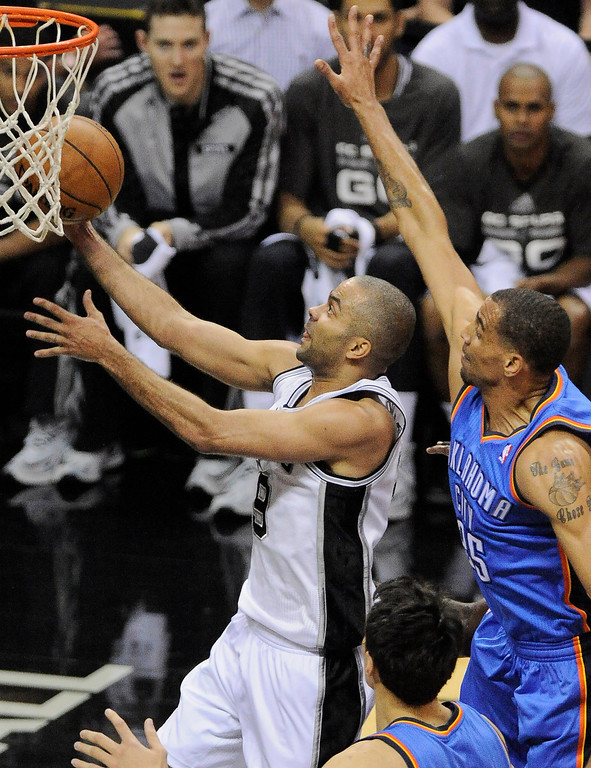 . San Antonio Spurs guard Tony Parker, left, of France, shoots against Oklahoma City Thunder guard Thabo Sefolosha, of Switzerland, during the first half of Game 2 of the Western Conference finals NBA basketball playoff series, Wednesday, May 21, 2014, in San Antonio. (AP Photo/Darren Abate)