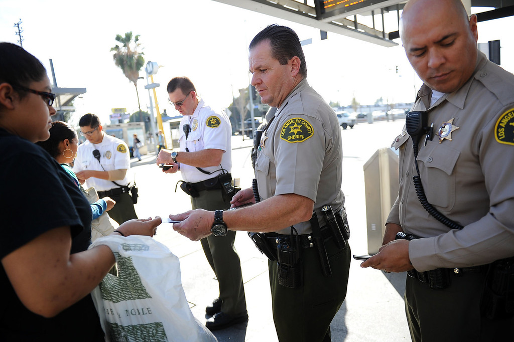 . LA County Sheriff deputies checks bus riders TAP cards during an Orange Line fare enforcement operation at the Van Nuys Orange Line Station February 25, 2014.  Officials from Metro and the Los Angeles Sheriff\'s Department Transit Services Bureau announced a new two-pronged effort to cut down on fare-evaders on the Orange Line by improving communications and beefing up enforcement.(Andy Holzman/Los Angeles Daily News)