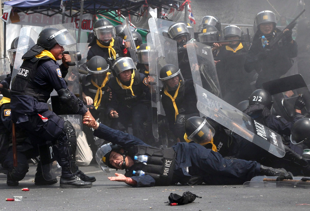 . An injured Thai riot police officer (C-B) is helped by his colleagues after a bomb attack during clashes with anti-government protesters in Bangkok, Thailand, 18 February 2014. One Thai policeman was killed and others sustained injuries from a bomb shrapnel during a crackdown on anti-government protesters in Bangkok, media reports said.  EPA/PETER CHAN
