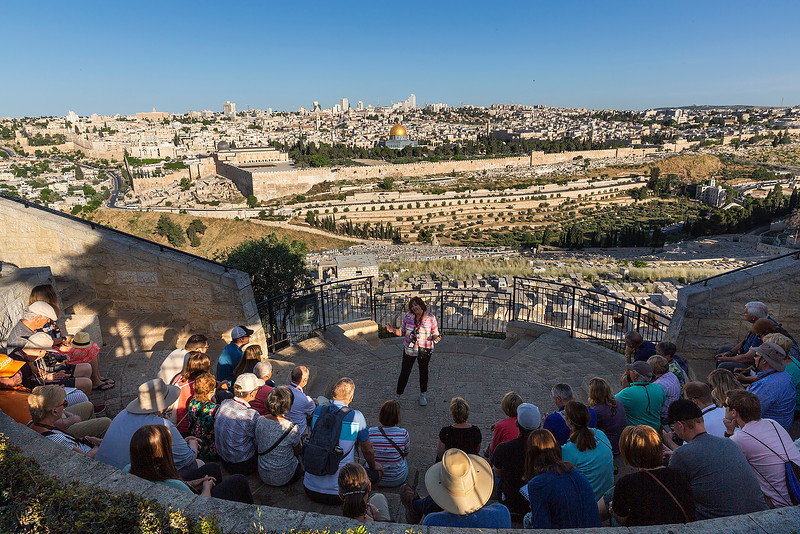 A tour guide informing her group above Jerusalem