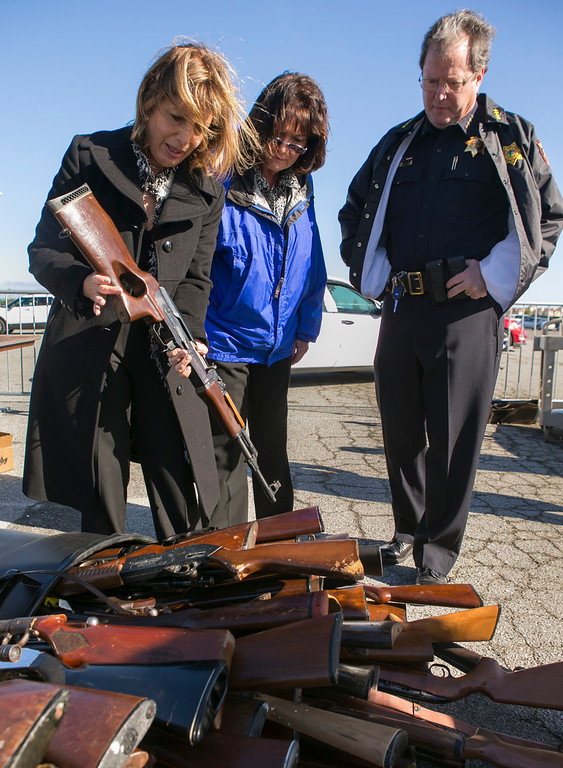 . Congresswoman Jackie Speier,left, (D-San Francisco/San Mateo), San Mateo County Supervisor Adrienne Tissier, middle, and San Mateo County Sheriff Greg Munks inspect an AK-47 that was turned in.