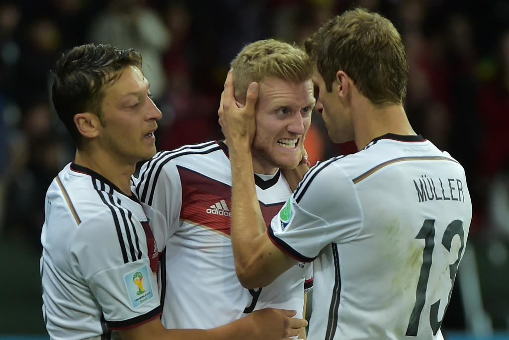. Germany\'s forward Andre Schuerrle celebrates (C) with his teammates Germany\'s forward Thomas Mueller (R) and Germany\'s midfielder Mesut Ozil after scoring a goal during the first half of extra-time in the Round of 16 football match between Germany and Algeria at Beira-Rio Stadium in Porto Alegre during the 2014 FIFA World Cup on June 30, 2014.    GABRIEL BOUYS/AFP/Getty Images