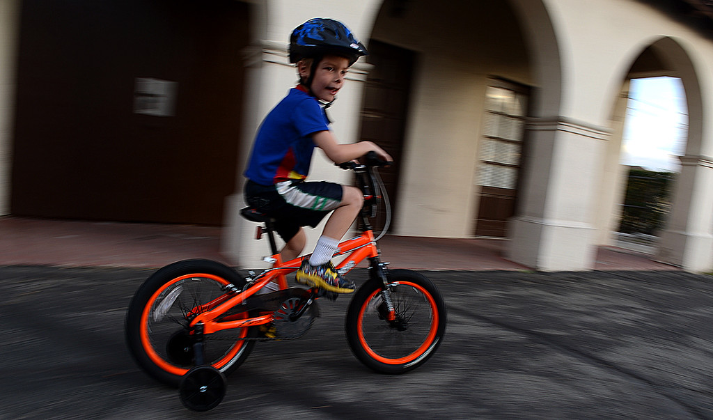. Alexander Williams, 5, takes his new bicycle for a ride. Southern California Honda Dealers� Helpful Guys in Blue hosted a Santa�s Workshop Monday December 16, 2013 building bicycles for children of the Westside Kinship Support Program at St Paul\'s Methodist Church. There was also cookie decorating, face painting, and a visit from Pedals the Clown. The Westside Kinship Support Program is a support system for caregivers who step in to raise extended family members� children who have been separated from or who have lost their parents.
