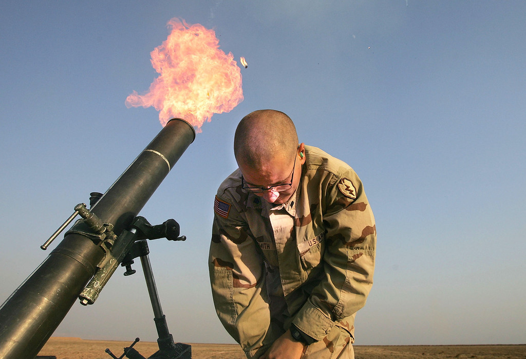""". Spc. Franklin Smith pulls away as a 120mm mortar blasts out of a tube January 17, 2005 at the edge of the US airbase in Tal Afar, Iraq. US mortaring teams frequently fire \""""harassment and interdiction\"""" mortar fusillades from the base to suspected enemy positions or watched areas nearby. (Photo by Chris Hondros/Getty Images)"""