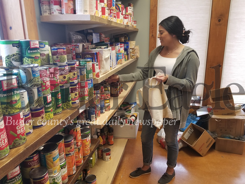 SRU senior Elizabeth Hernandez stocks the food pantry at the McCoskey Center that helps students with food insecurity. Photo by Nathan Bottiger.