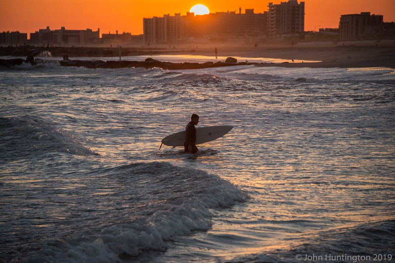 A surfer walks from the ocean at sunset in the Rockaways, Queens, New York City.