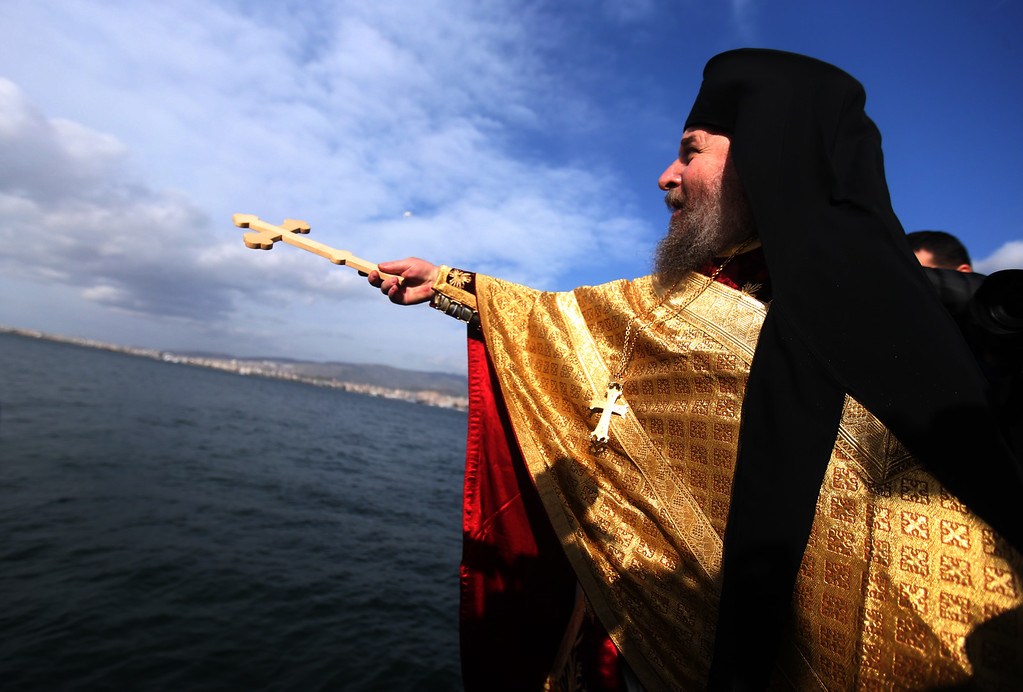 . Orthodox priest Kyrillos Sykis throws a wooden cross into the water during an Epiphany ceremony in Izmir, Turkey, Wednesday, Jan. 6, 2016. The traditional Epiphany ceremony marks the Epithany when Ecumenical Patriarch Bartholomew I, the spiritual leader of the world\'s Orthodox Christians, or an Orthodox priest throws a simple wooden cross into the water and swimmers race to be the first to retrieve it. In Izmir, Turkey�s third largest city, it was the first �official� Epiphany ceremony there since the end of a Greek-Turkey war nearly a century ago.(AP Photo/Emre Tazegul)