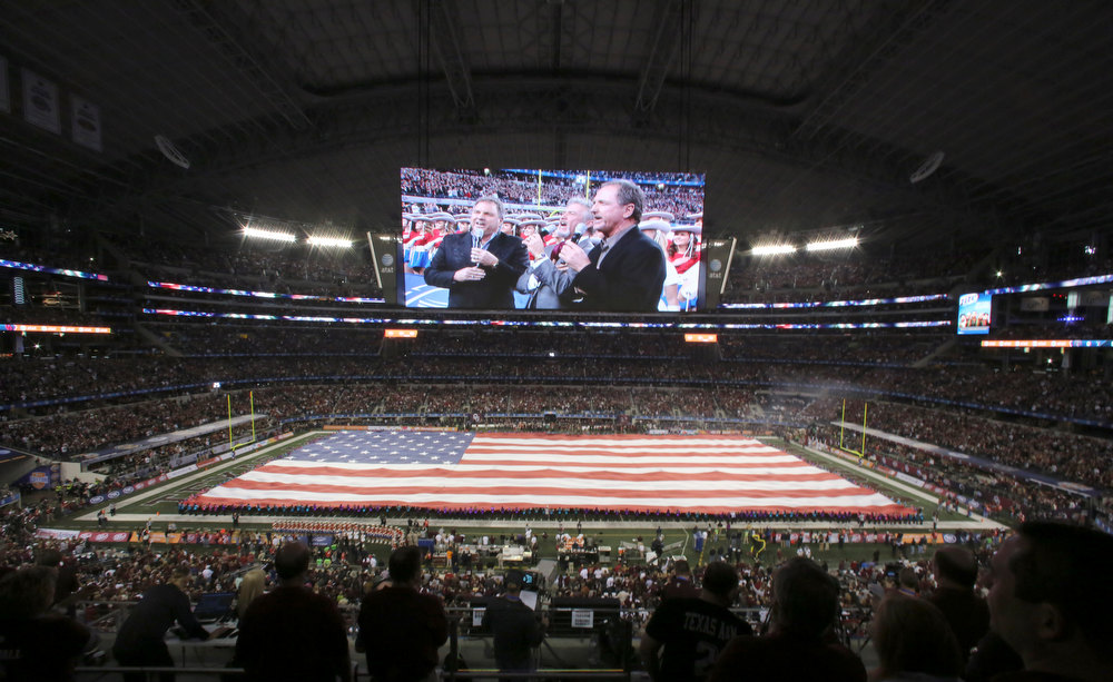 Description of . The Gatlin Brothers, displayed on a video screen, sing the national anthem before the Cotton Bowl NCAA college football game between Oklahoma and Texas A&M at Cowboys Stadium on Friday, Jan. 4, 2013, in Irving, Texas. (AP Photo/LM Otero)