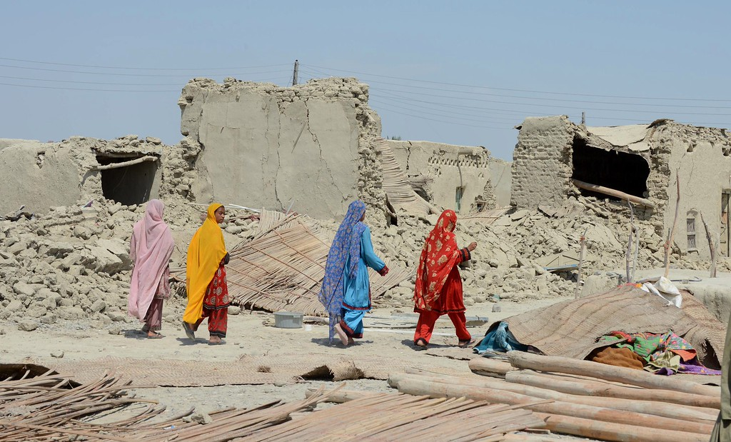 . Pakistani earthquake survivors walk past collapsed mud houses at Labach area, in the earthquake-devastated district of Awaran on September 26, 2013.  AFP PHOTO / Banaras KHAN/AFP/Getty Images