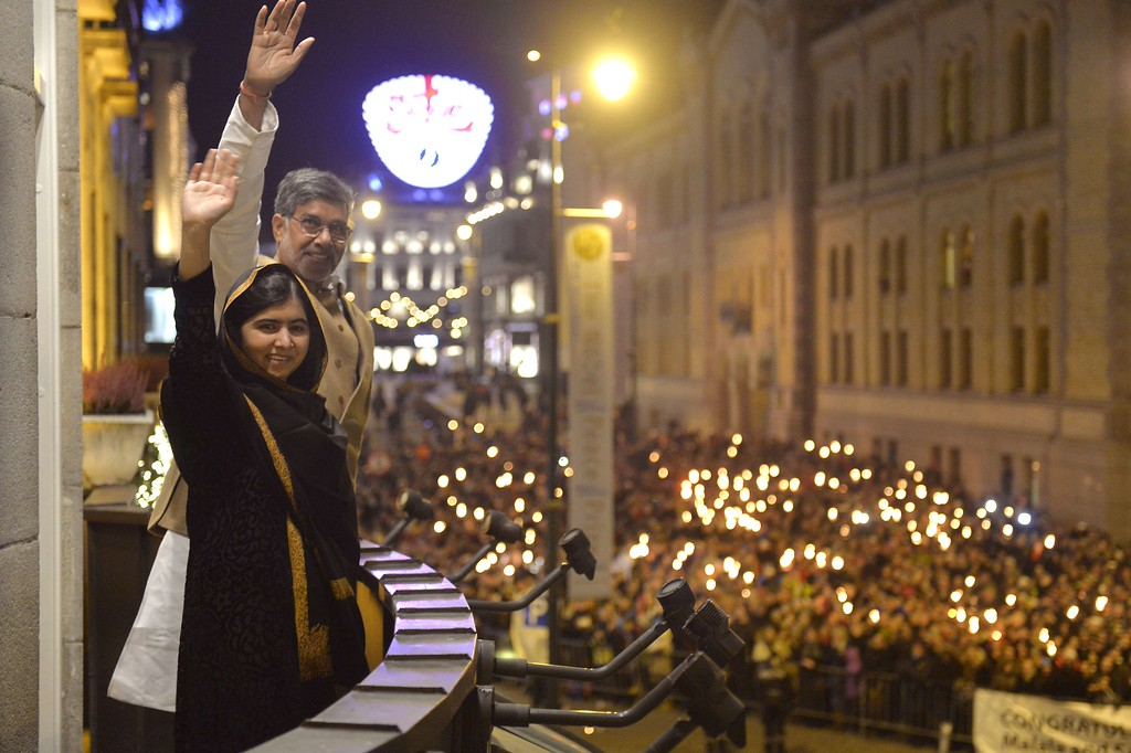 . Nobel Peace Prize 2014 laureates Pakistan\'s Malala Yousafzai (L) and India\'s Kailash Satyarthi wave to people holding torches from the bacony of the Grand Hotel ahead of the Nobel Banquet following the Nobel Peace Prize ceremony in Oslo on December 10, 2014. The 17-year-old Pakistani girls\' education activist Malala Yousafzai known as Malala shares the 2014 peace prize with the Indian campaigner Kailash Satyarthi, 60, who has fought for 35 years to free thousands of children from virtual slave labour.   AFP PHOTO / POOL / TORSTEIN BOETORSTEIN BOE/AFP/Getty Images