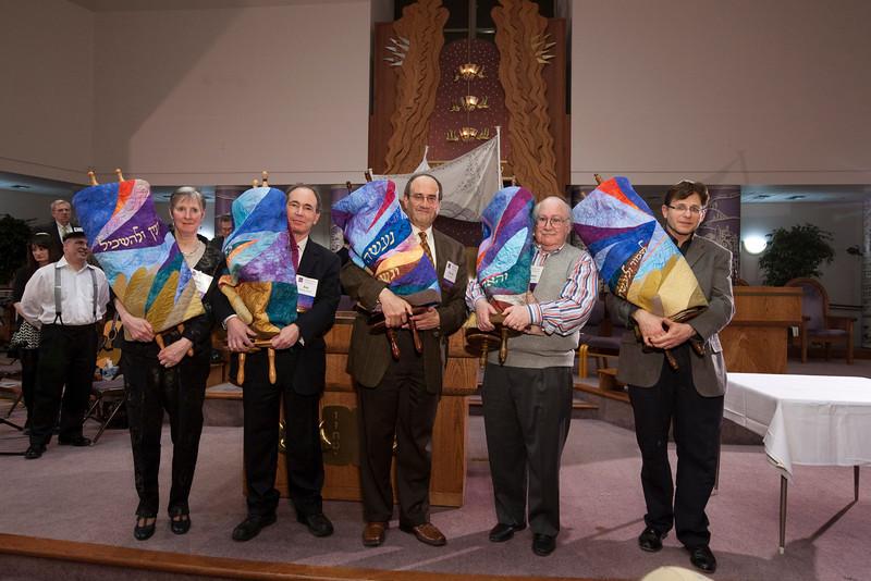 The new Torah scroll (c) joins the four senior scrolls on the bimah