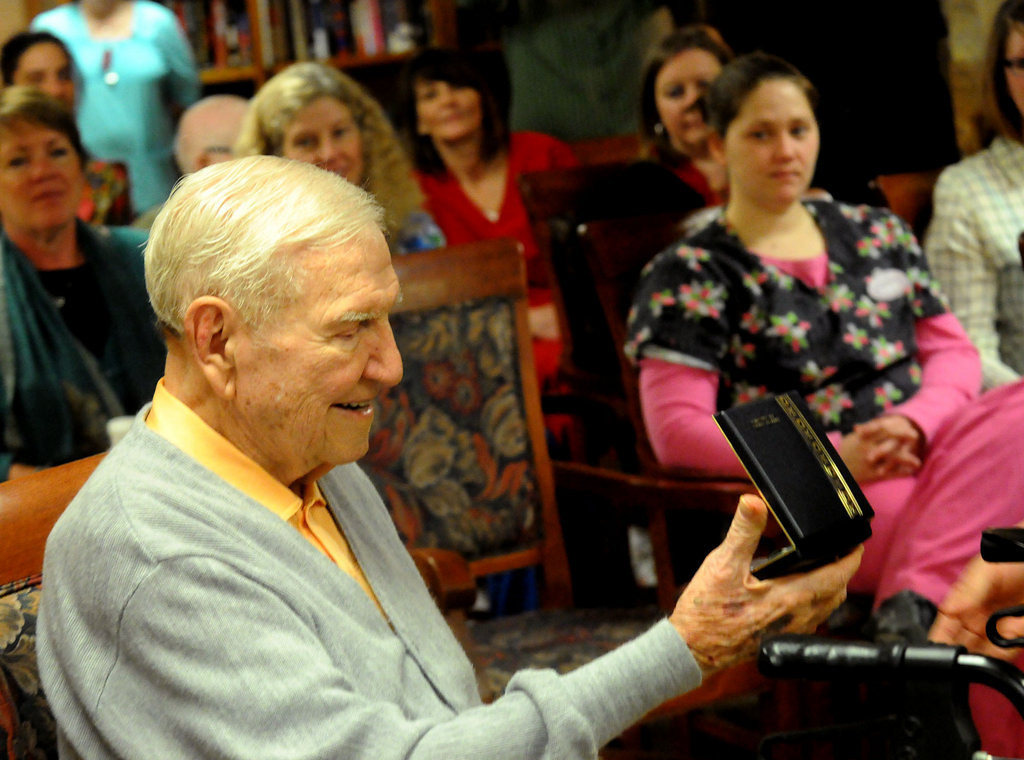 . Surrounded by his fellow residents and staff at Red Cedar Canyon Assisted Living Center in Hudson, Burrows looks over his Navy Commendation Medal.  (Pioneer Press: John Doman)