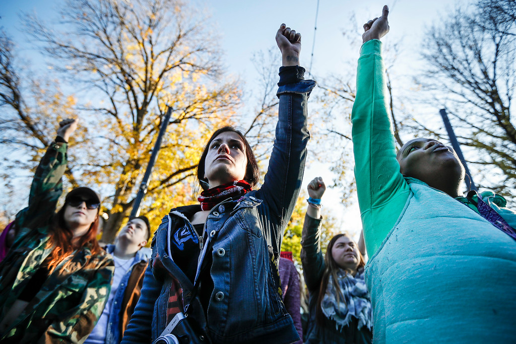 . Protestors raise their fists in defiance as they gather in Washington Park after a mistrial was declared due to a hung jury in the murder trial against Ray Tensing, Saturday, Nov. 12, 2016, in Cincinnati. Tensing, a white former University of Cincinnati police officer, was charged with murder in the shooting of Sam DuBose, an unarmed black motorist, while on duty during a routine traffic stop on July 19, 2015. (AP Photo/John Minchillo)