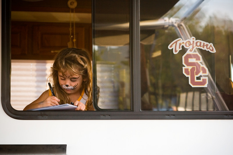 Sophia appears in the window, drawing something on the back of a notebook