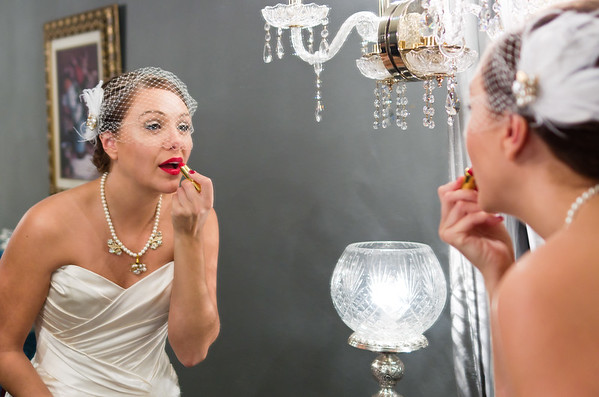 Bride applies red lipstick