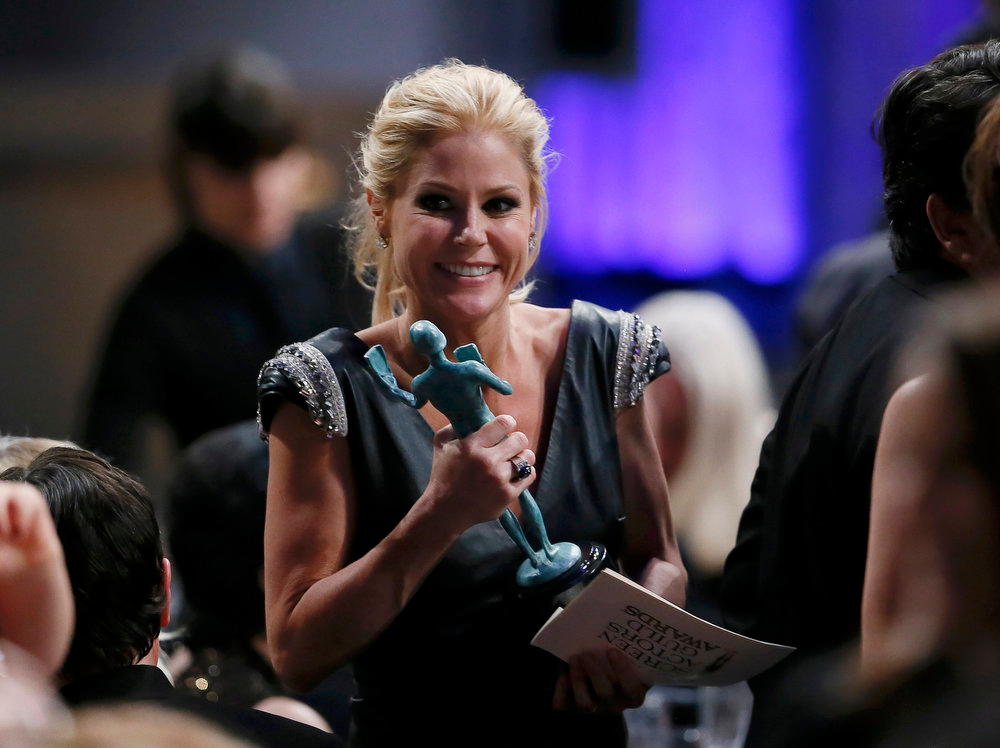 ". Actress Julie Bowen returns to her table with her award for outstanding performance by an ensemble in a comedy series for ""Modern Family\"" at the 19th annual Screen Actors Guild Awards in Los Angeles, California January 27, 2013.   REUTERS/Lucy Nicholson"