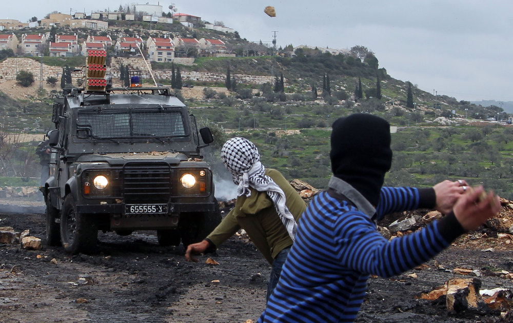 Description of . Palestinian protesters rethrow stones at israeli soldiers during clashes following a protest against the expropriation of Palestinian land by Israel on February 1, 2013 in the village of Kafr Qaddum, near Nablus, in the occupied West Bank. JAAFAR ASHTIYEH/AFP/Getty Images