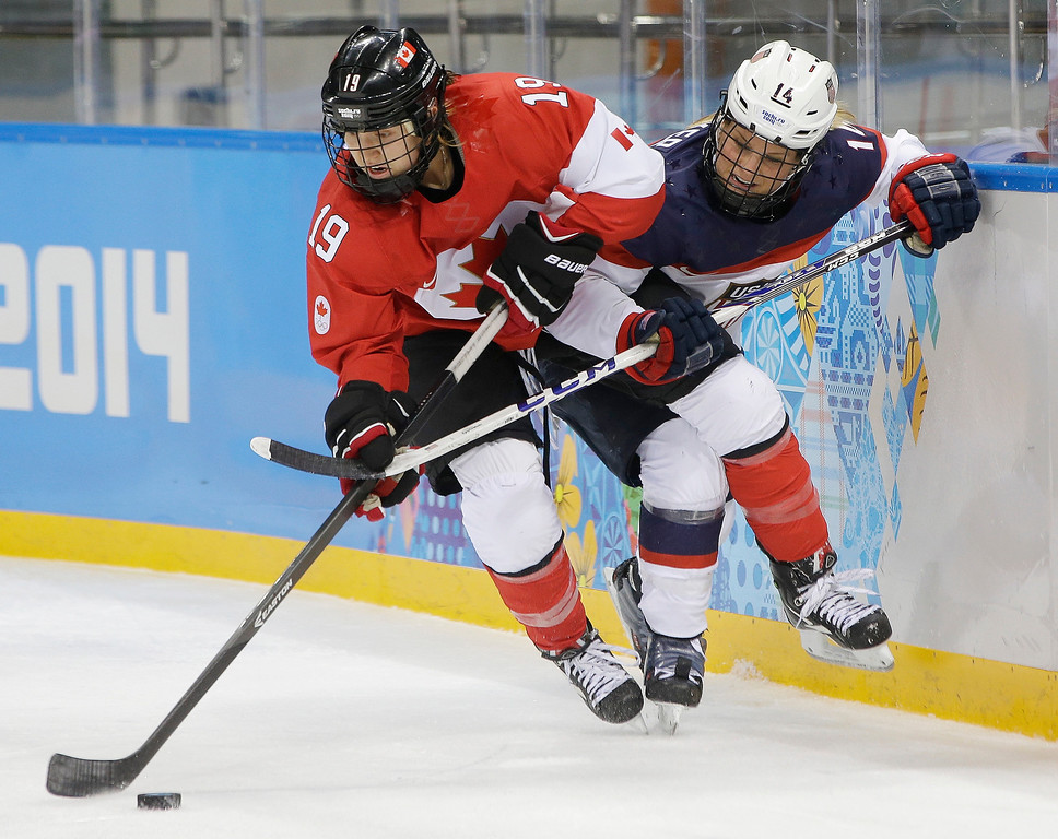 . Brianne Jenner of Canada and Brianna Decker of the United States battle up again the boards for control of the puck during the second period of the 2014 Winter Olympics women\'s ice hockey game at Shayba Arena, Wednesday, Feb. 12, 2014, in Sochi, Russia. (AP Photo/Matt Slocum)