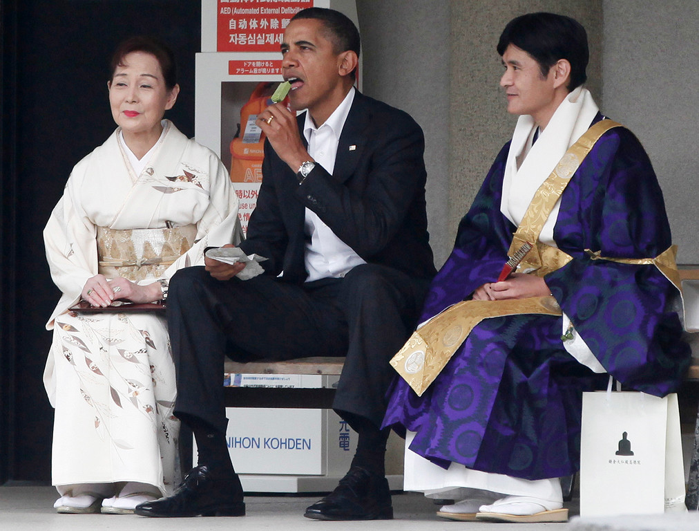 . President Barack Obama eats green tea ice cream as he visits the Great Buddha of Kamakura with Michiko Sato, temple director, and Takao Sato, the 15th chief monk of the temple, at Kotokuin Temple in Kamakura, Japan,  Sunday, Nov. 14, 2010. (AP Photo/Charles Dharapak)
