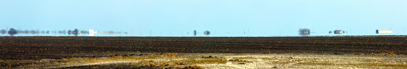 On the way from Houston to Fulton, TX: Panorama of a mirage over the flat fields of Refugio County, plowed for the Spring planting.
