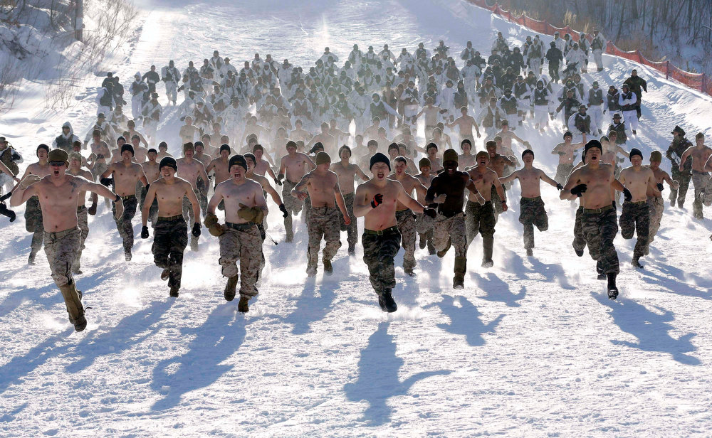 . Shirtless South Korean Marines and their U.S. counterparts from 3-Marine Expeditionary Force 1st Battalion from Kaneho Bay, Hawaii, run on a snow covered field during their Feb. 4-22 joint military winter exercise in Pyeongchang, east of Seoul, South Korea, Thursday, Feb. 7, 2013. More than 400 marines from the two countries participated in the joint winter exercise held for the first time in South Koreas. (AP Photo/Lee Jin-man)