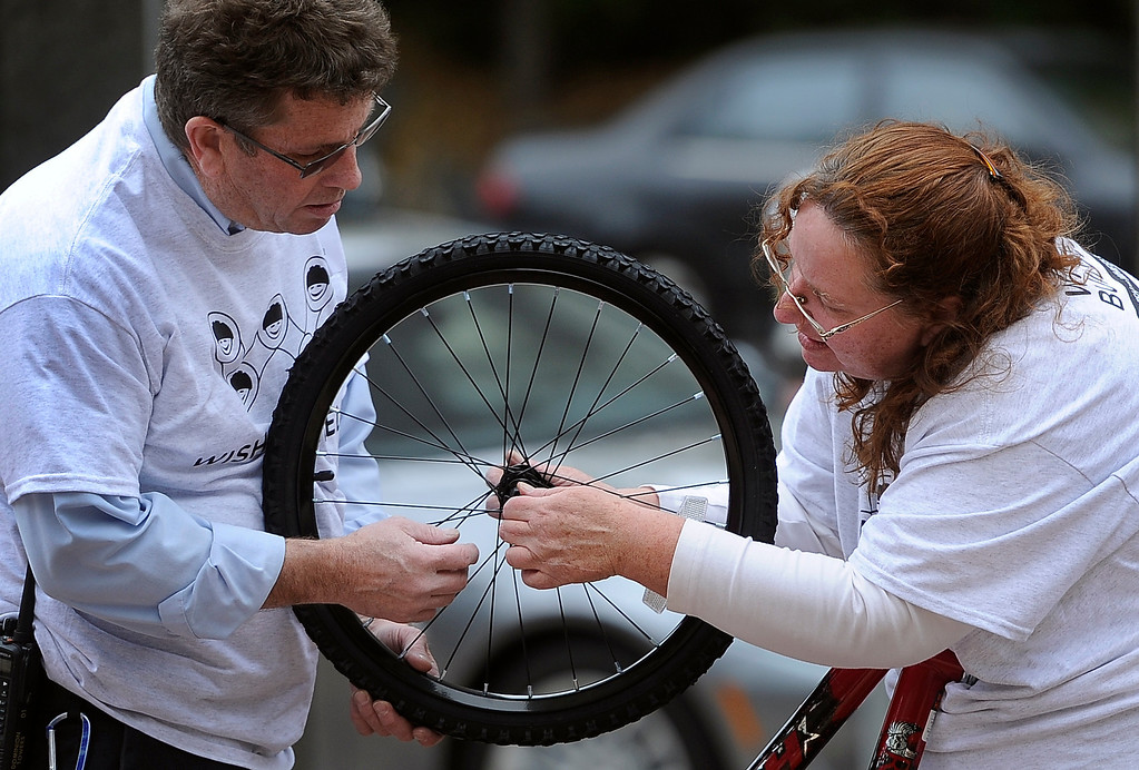 . DENVER, CO - Oct. 11: Outside the Tabor Center downtown, volunteers Julie Muhovich, right, and Jim Wessels prepare a wheel for one of the bikes. Wish for Wheels and its volunteers build and give away over one hundred bikes to kindergarteners and first-graders at Smith Renaissance School in Park Hill. Wish for Wheels says its goal with one-in-five children liven in poverty, is to give as many kids as possible their first brand new bike and helmet. (Photo By Kathryn Scott Osler/The Denver Post)