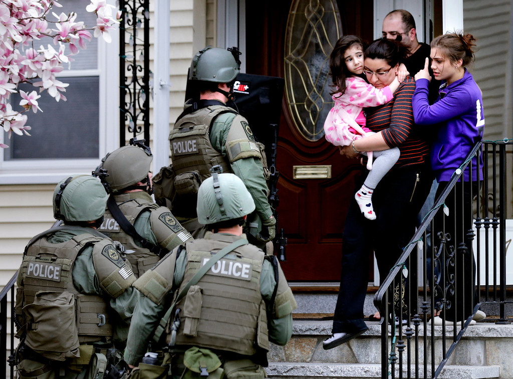 . A woman carries a girl from their home as a SWAT team searching for a suspect in the Boston Marathon bombings enters the building in Watertown, Mass., Friday, April 19, 2013. Two suspects in the Boston Marathon bombing killed an MIT police officer, injured a transit officer in a firefight and threw explosive devices at police during their getaway attempt in a long night of violence that left one of them dead and another still at large Friday, authorities said as the manhunt intensified for a young man described as a dangerous terrorist. (AP Photo/Charles Krupa)