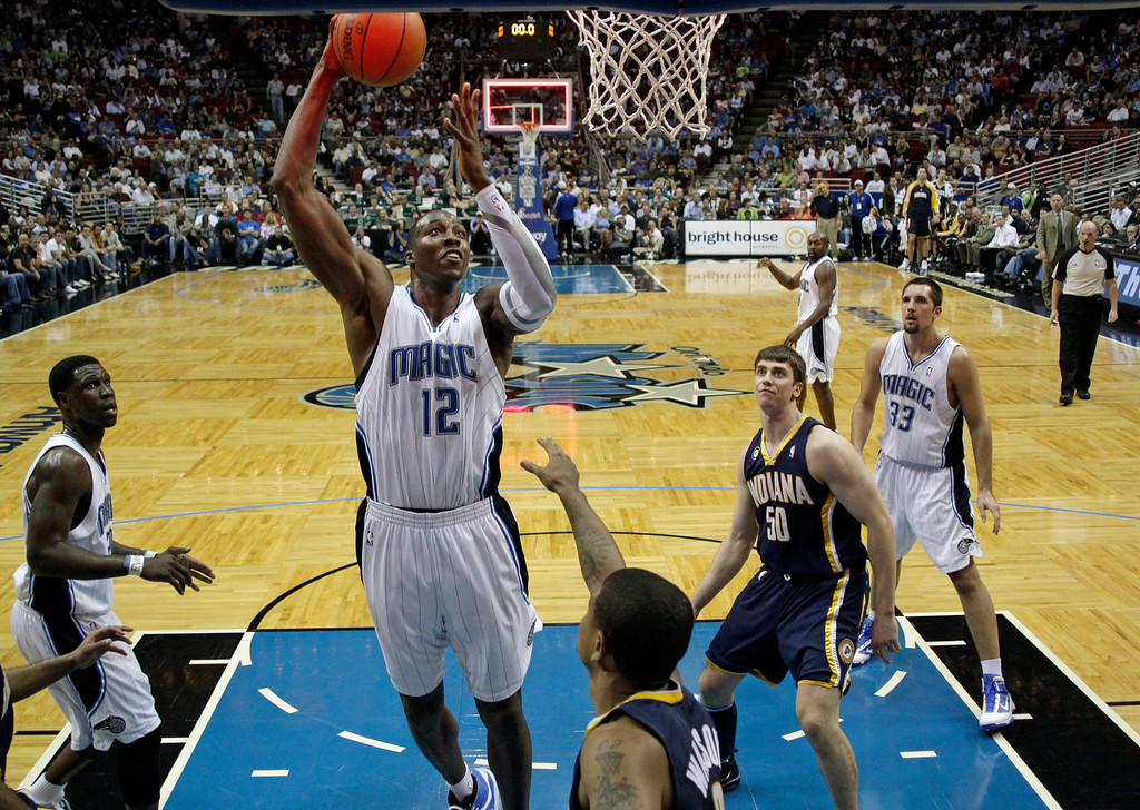 . Orlando Magic center Dwight Howard (12) tries but can\'t get a shot off before the buzzer in front of Indiana Pacers forward Tyler Hansbrough (50) at the end of the first quarter of an NBA basketball game in Orlando, Fla., Monday, Dec. 14, 2009. Orlando won 106-98.(AP Photo/John Raoux)