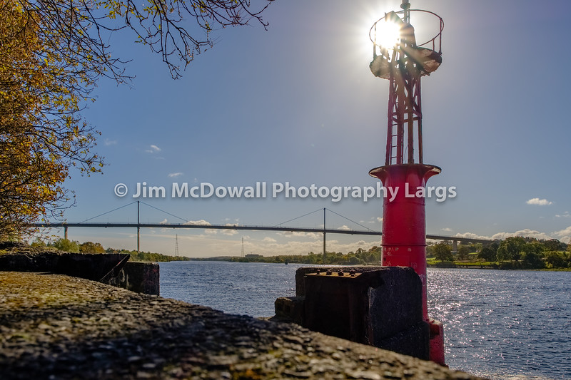Old Port Beacon on the River Clyde with Erskine Bridge in the Background and the sun behind the Beacon.