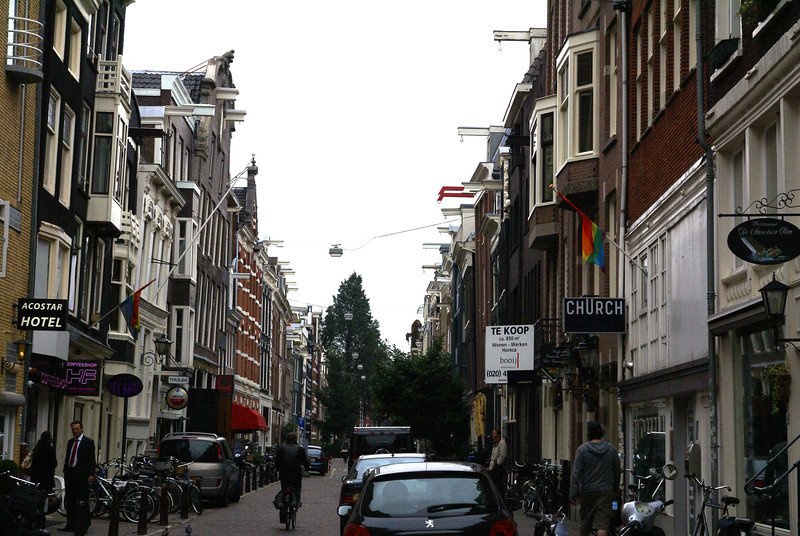 Amsterdam street with hoists on buildings. The leaning in of the buildings is not an illusion. In order to clear the side of the building the top has to stick out.