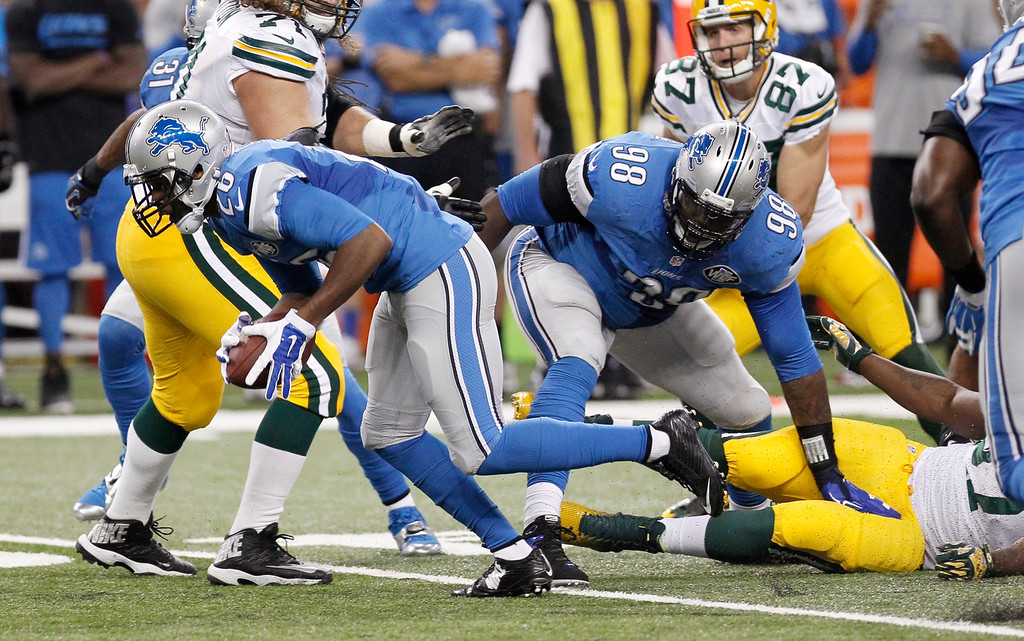. Detroit Lions strong safety Don Carey, ront left, picks up a fumble by Green Bay Packers running back Eddie Lacy and runs it back for a 40-yard touchdown during the first half of an NFL football game in Detroit, Sunday, Sept. 21, 2014. (AP Photo/Duane Burleson)