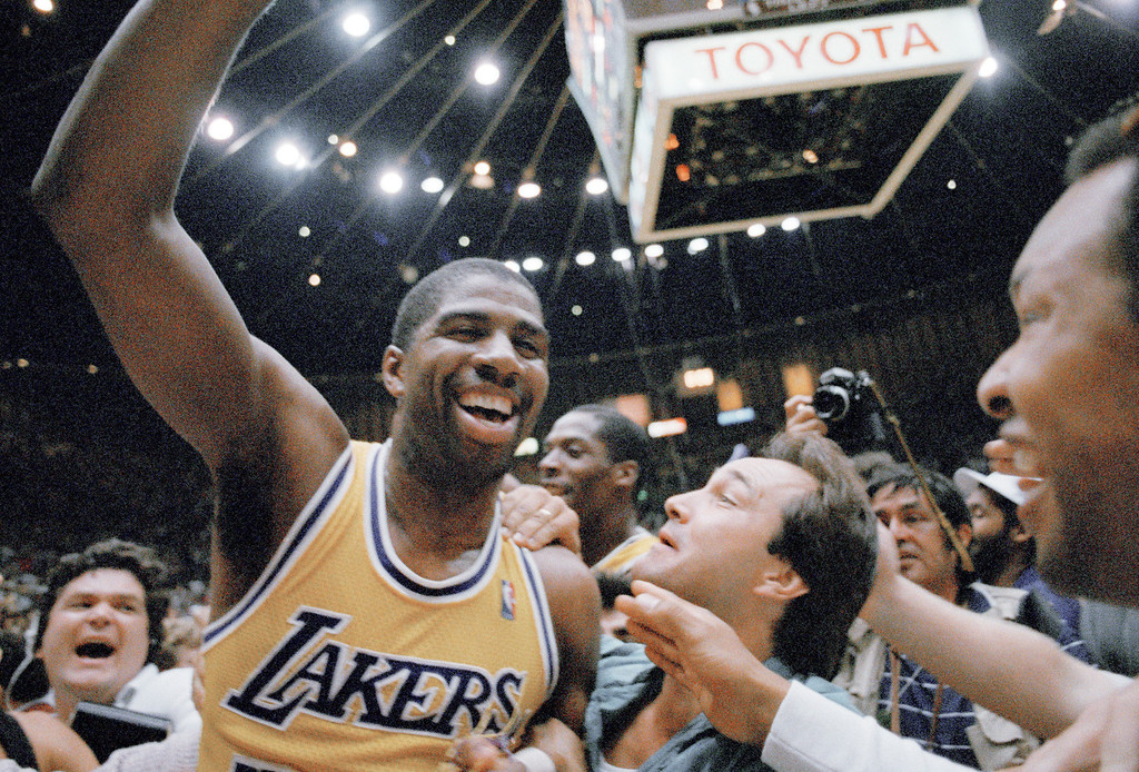 . Los Angeles Lakers\' Magic Johnson shows his elation as he\'s swarmed by fans as he leaves the court after Lakers defeated Boston Celtics, 106-93, to win the NBA championship at the Forum in Inglewood, California on June 14, 1987. Johnson was named the MVP of the series. (AP Photo/Reed Saxon)