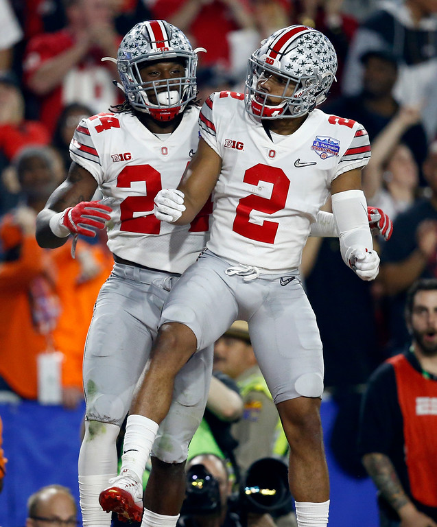 . Ohio State safety Malik Hooker (24) celebrates his interception against Clemson with teammate Marshon Lattimore (2) during the first half of the Fiesta Bowl NCAA college football playoff semifinal, Saturday, Dec. 31, 2016, in Glendale, Ariz. (AP Photo/Ross D. Franklin)