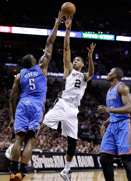 . San Antonio Spurs\' Tim Duncan (21) shoots over Oklahoma City Thunder\'s Kendrick Perkins (5) and Serge Ibaka, right, during the first half of Game 5 of the Western Conference finals NBA basketball playoff series, Thursday, May 29, 2014, in San Antonio. (AP Photo/Eric Gay)