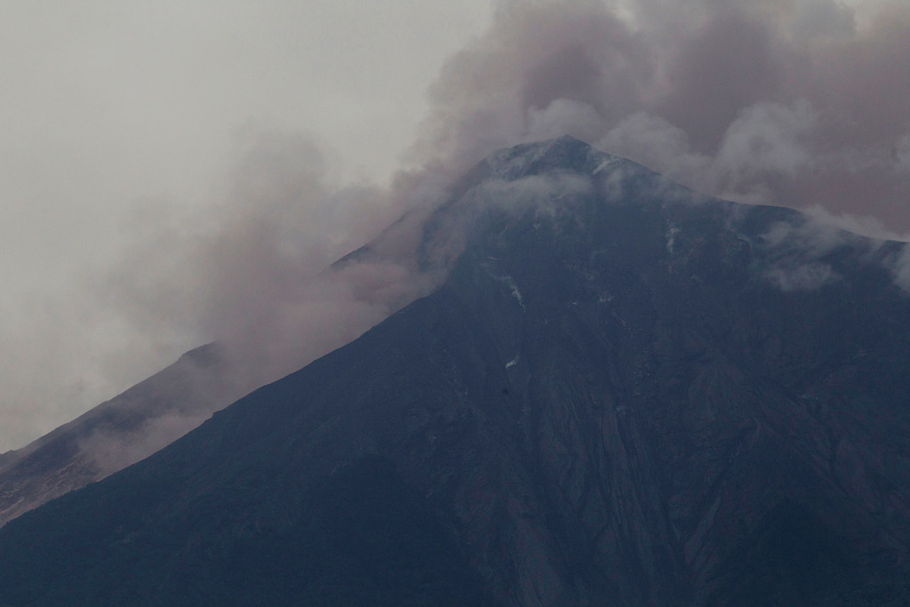 . Volcan de Fuego, or Volcano of Fire, blows outs a thick cloud of ash, as seen from Alotenango, Guatemala, Sunday, June 3, 2018. One of Central America\'s most active volcanos erupted in fiery explosions of ash and molten rock Sunday, killing people and injuring many others while a towering cloud of smoke blanketed nearby villages in heavy ash. (AP Photo/Luis Soto)