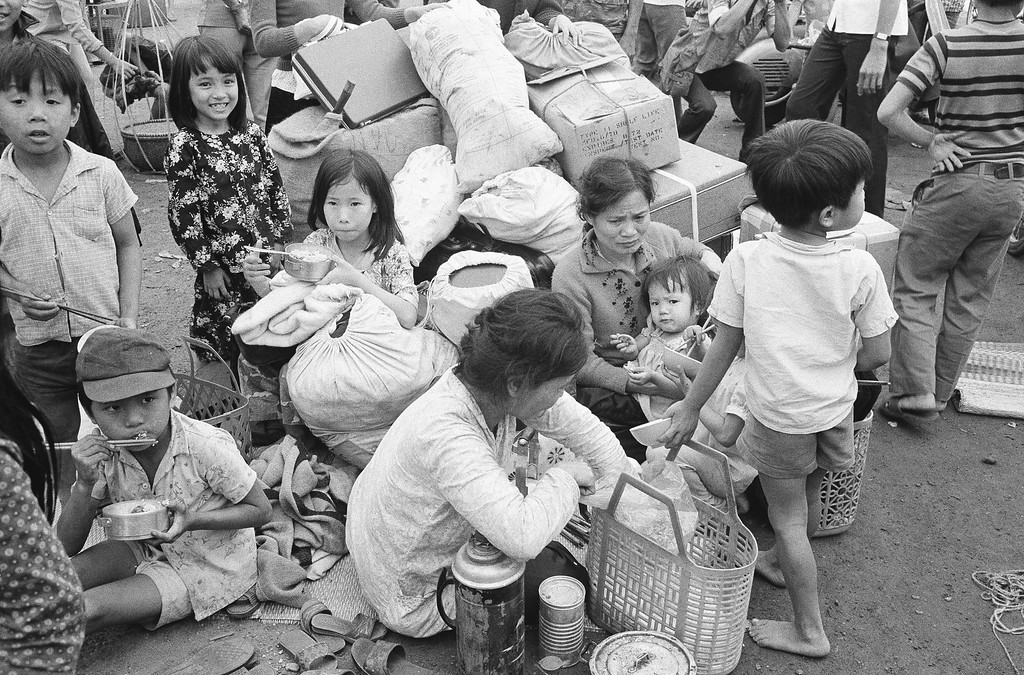 . Their household goods in a haphazard pile, a South Vietnamese refugee family takes time out for lunch at Da Nang in Vietnam, March 28, 1975, where they are waiting to be relocated after fleeing from the Northern provinces. (AP Photo/Phuoc)