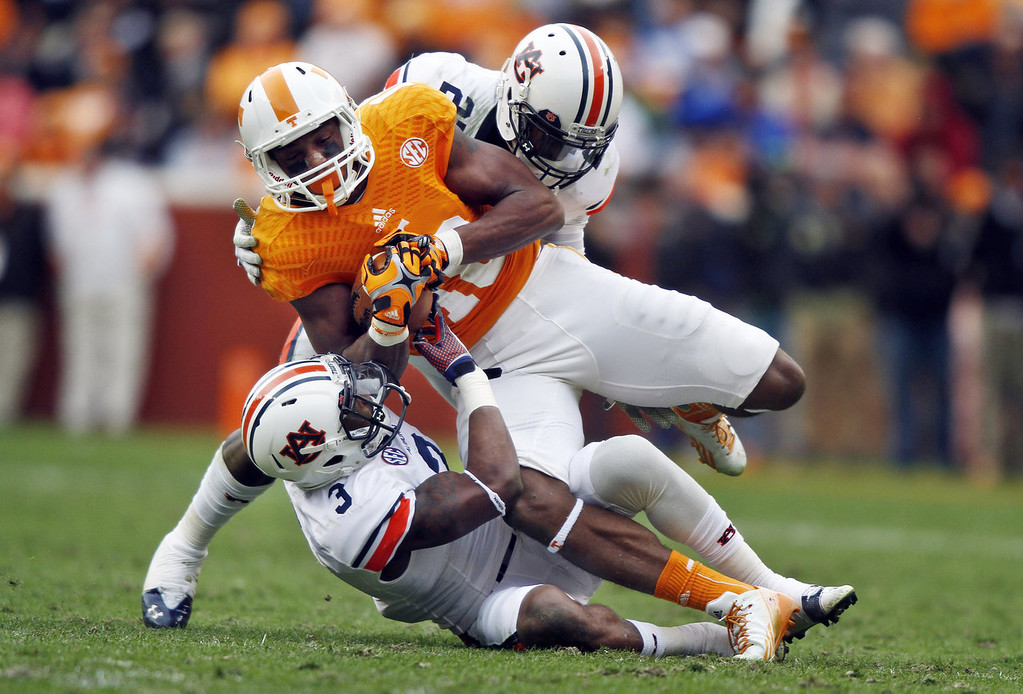 . Tennessee wide receiver Jason Croom, center, is tackled by Auburn defensive back Jonathan Jones (3) and defensive back Robenson Therezie (27) in the second half of an NCAA college football game on Saturday, Nov. 9, 2013, in Knoxville, Tenn. (AP Photo/Wade Payne)