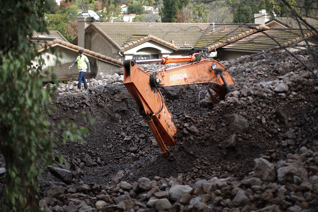 . Part of a large backhoe is exposed as workers retrieve the machine that was buried under rocks and mud during a attempt to save homes from debris flows overnight as a powerful storm that has been lashing northern California moves southward on December 12, 2014 in Camarillo Springs neighborhood of Camarilla, California.   (Photo by David McNew/Getty Images)