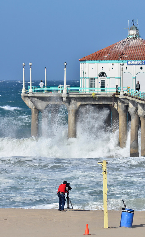 . A cameraman captures big waves hitting the Manhattan Beach Pier Monday 4-8-13. Photo by Brad Graverson