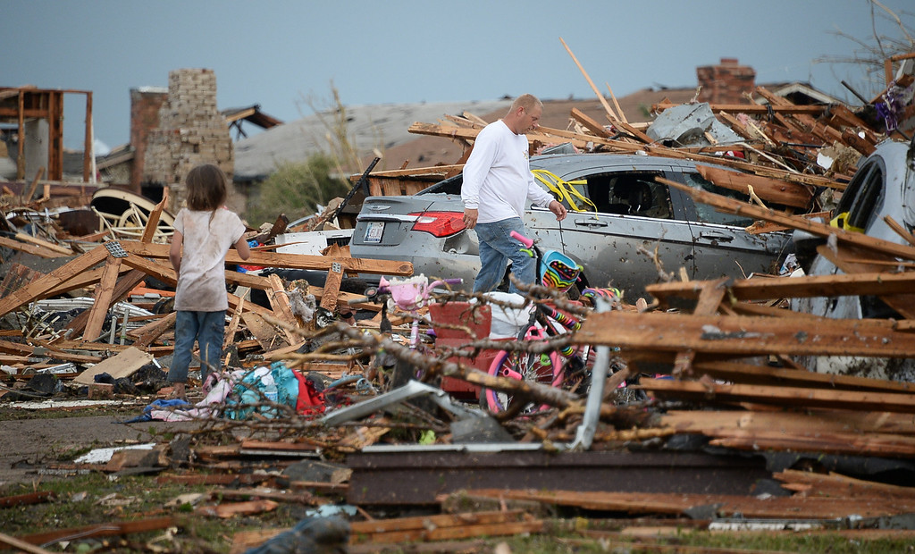 . Local Neighbors look through the mangeld mess of homes.